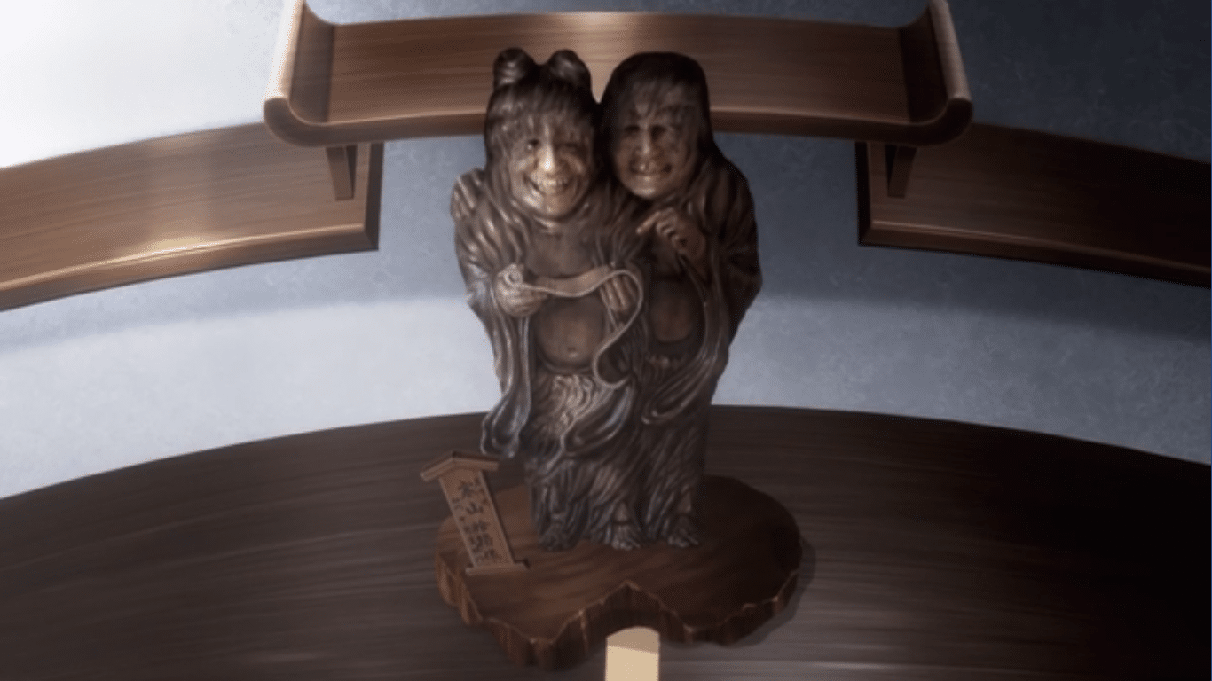 An old statue of two Chinese monks standing together on a wooden platform.