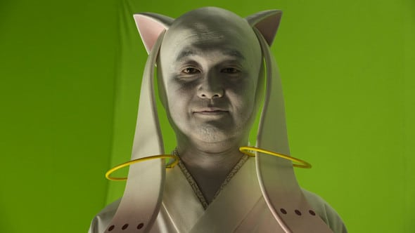 "Screenshot of ""Kyuubey"" from a live action anime parody of Madoka Magica, Magica Shirabe, where this cute alien is played by a full grown man."