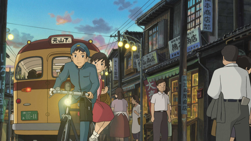 Umi and Shun ride a bike through town, a bus and sunset lit sky behind them