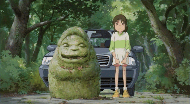 Chihiro stands angrily beside a happy, egg-shaped statue at the entrance of the park