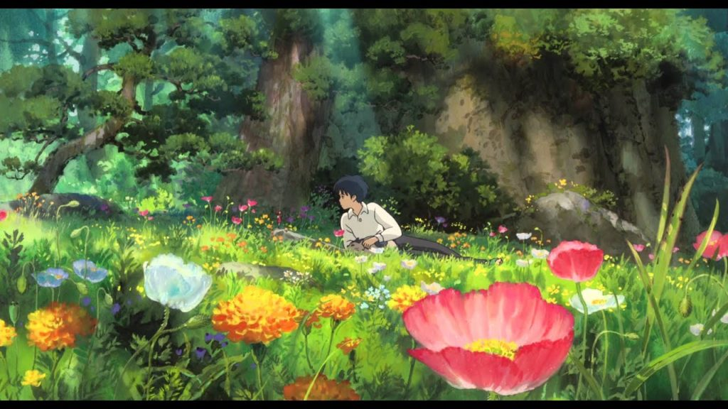 A boy lies in a garden of flowers and meets his tiny neighbor for the first time