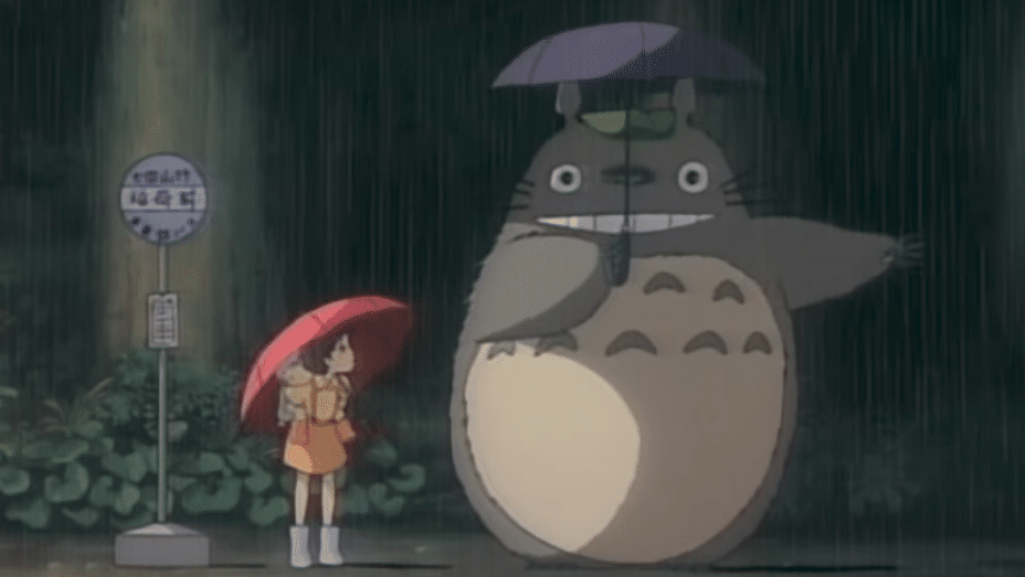 Totoro stands in the rain with Mei and Satsuki as they wait at a bus stop